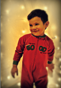 My youngest standing in front of a sheet with Christmas lights behind it!