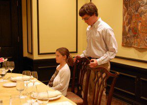 Eric helps Eleanor to her seat at the table.