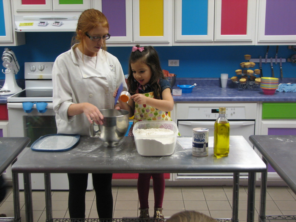 Birthday Girl Avery Getting Some Hands On Measuring Instructions From A YCA Chef