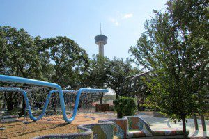 The Tower of the Americas is visible over the play structures at Yanaguana Garden in Hemisfair | Alamo City Moms Blog