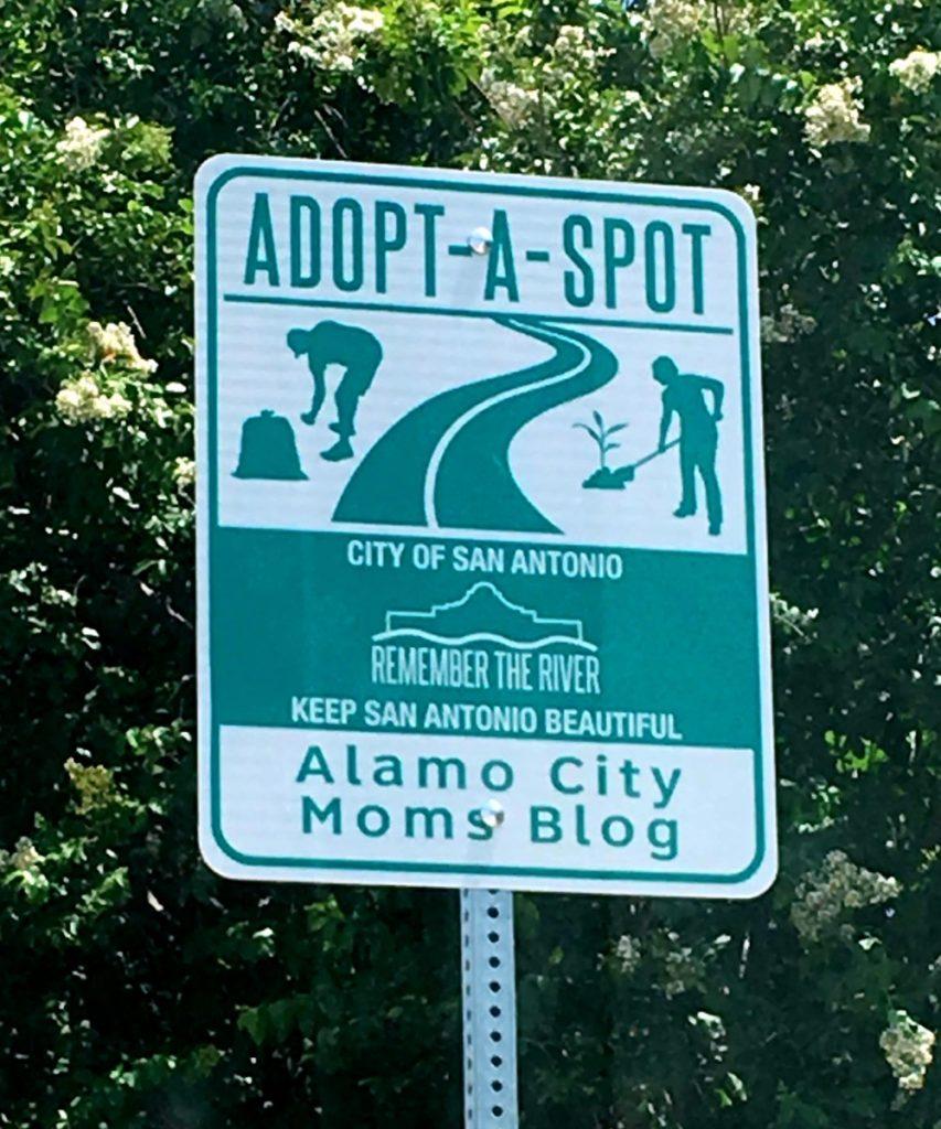 Sign along South Alamo Street near Hemisfair showing Alamo City Moms Blog's Adopt-A-Spot
