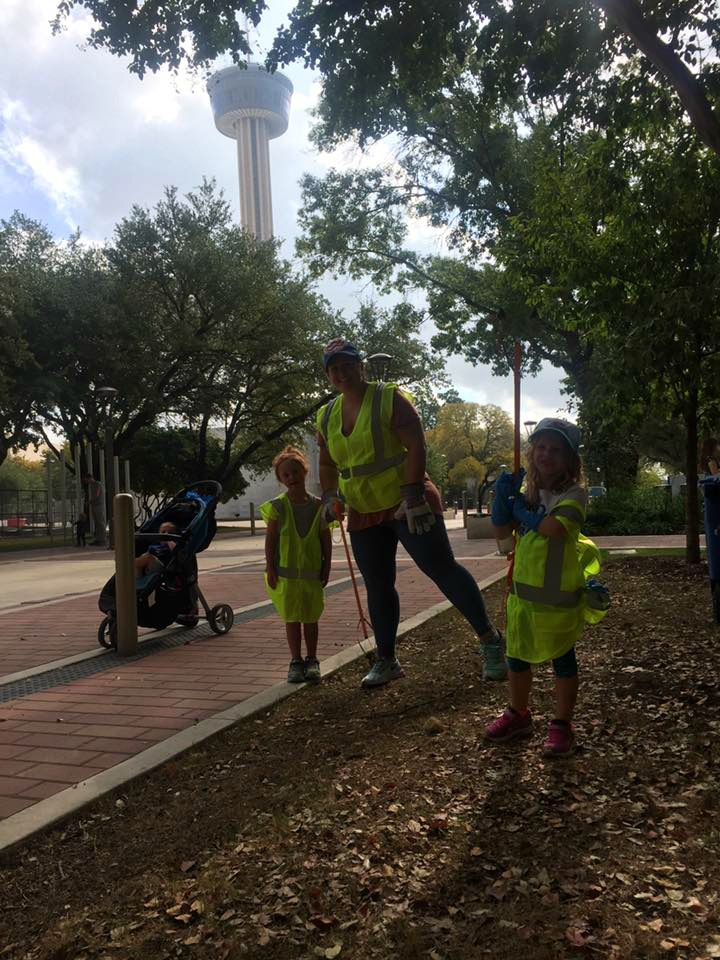 Alamo City Moms Blog contributor Danielle and family members at park cleanup at Hemisfair