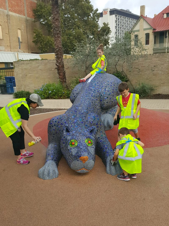 Alamo City Moms Blog contributors and family members at park cleanup at Hemisfair