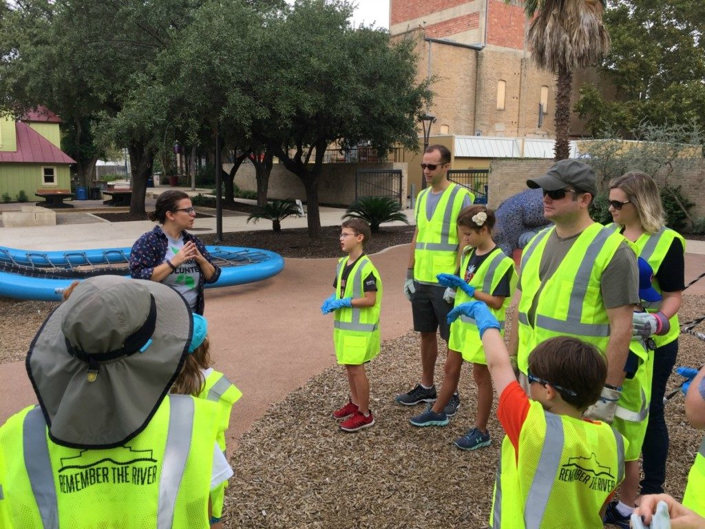Volunteer Coordinator Meredith Tilley leading Alamo City Moms Blog contributors and family members at park cleanup at Hemisfair