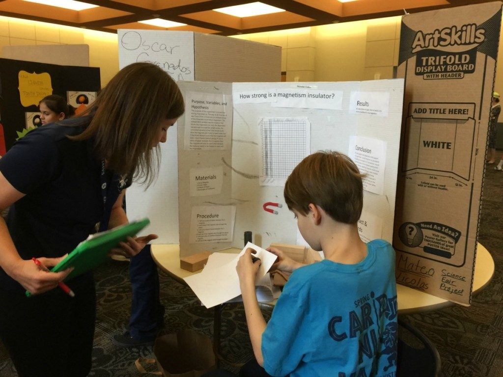 F.T. showing his science fair project to his teacher   Alamo City Moms Blog