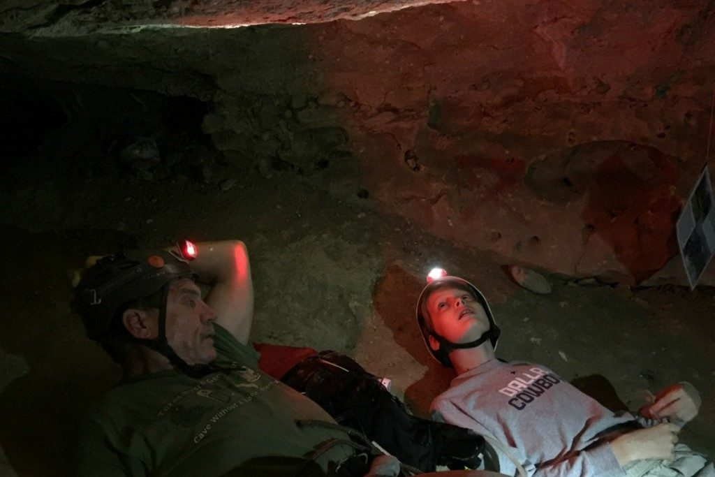 Guide and young explorer looking at bats in Robber Baron Cave in San Antonio, Texas | Alamo City Moms Blog