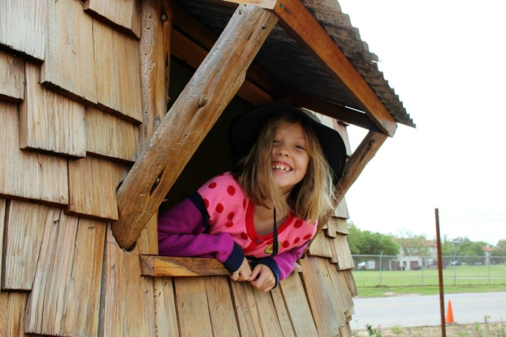 Girl peeking out the window of a playhouse at the Family Adventure Garden at the San Antonio Botanical Garden | Alamo City Moms Blog