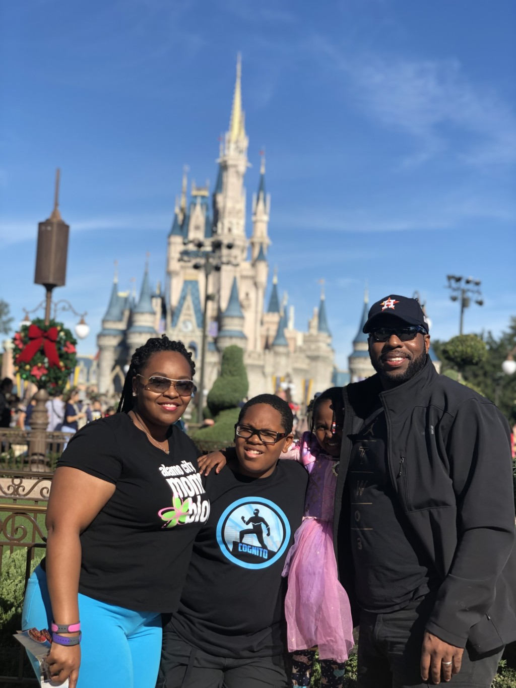 Family posing in front of Cinderella's castle