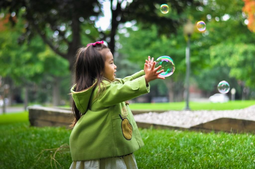 little girl holding bubbles