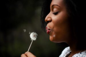 black woman in white top blowing dandelion
