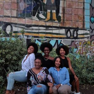 five Black women smiling and sitting on the ground
