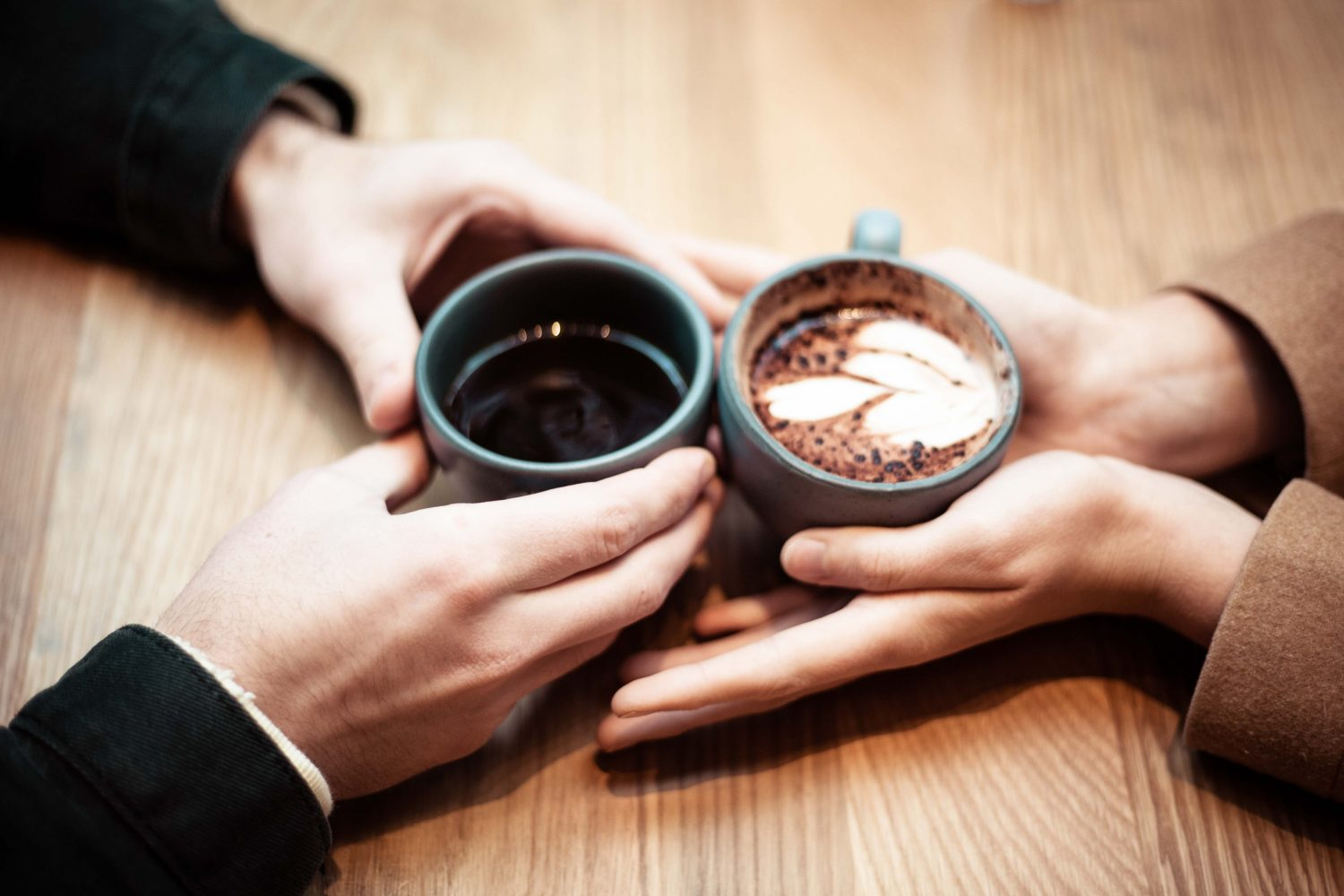 couple holding cups of coffee together on table