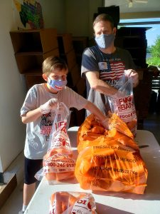 a father and son sorting carrots at the food bank