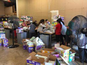 Families volunteering at the Texas Diaper Bank